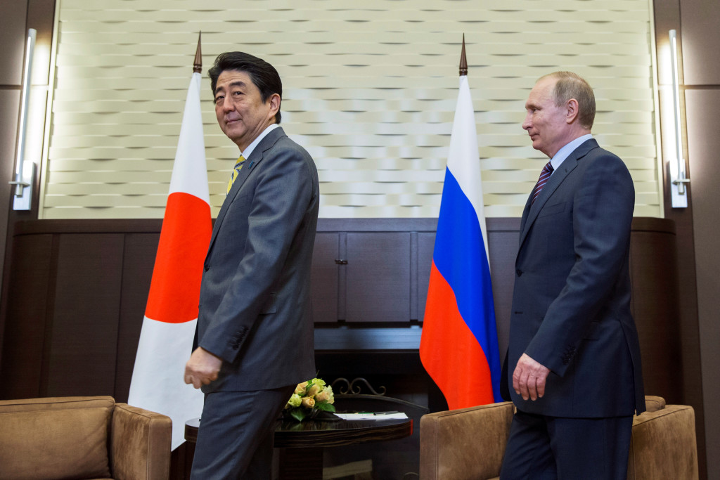 Russian President Vladimir Putin (R) and Japanese Prime Minister Shinzo Abe walk into a hall during a meeting in Sochi, Russia, May 6, 2016. REUTERS/Pavel Golovkin/Pool - RTX2D4DO