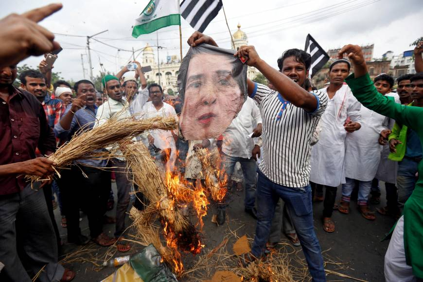 Protestors burn an image of Myanmar's leader Aung San Suu Kyi