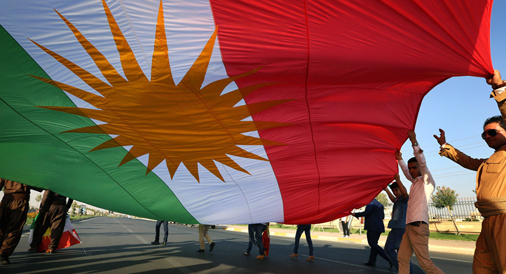 Supporters carry the Iraqi Kurdish flag