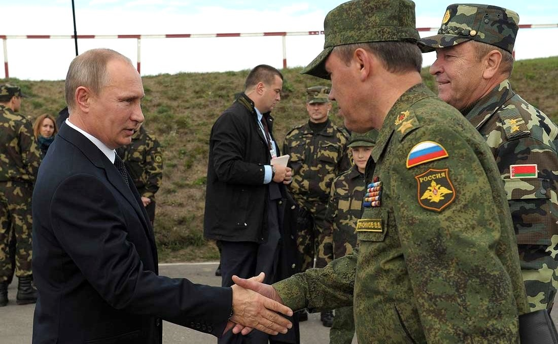 Vladimir Putin shakes the hand of a Russian and Belorussian soldiers engaged in Zapad exercises