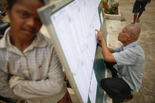 A man checks lists of voters at a polling station in suburbs of Phnom Penh, 2013