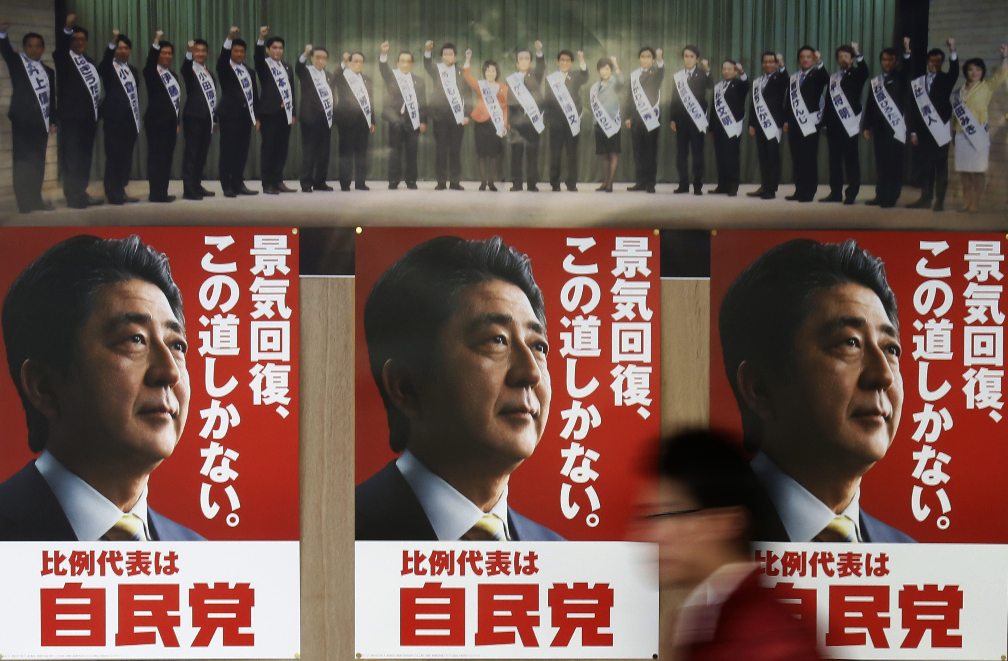 Staff member of Japan's ruling Liberal Democratic Party walks past election campaign posters showing Japan's Prime Minister Shinzo Abe at the LDP regional election office in Tokyo