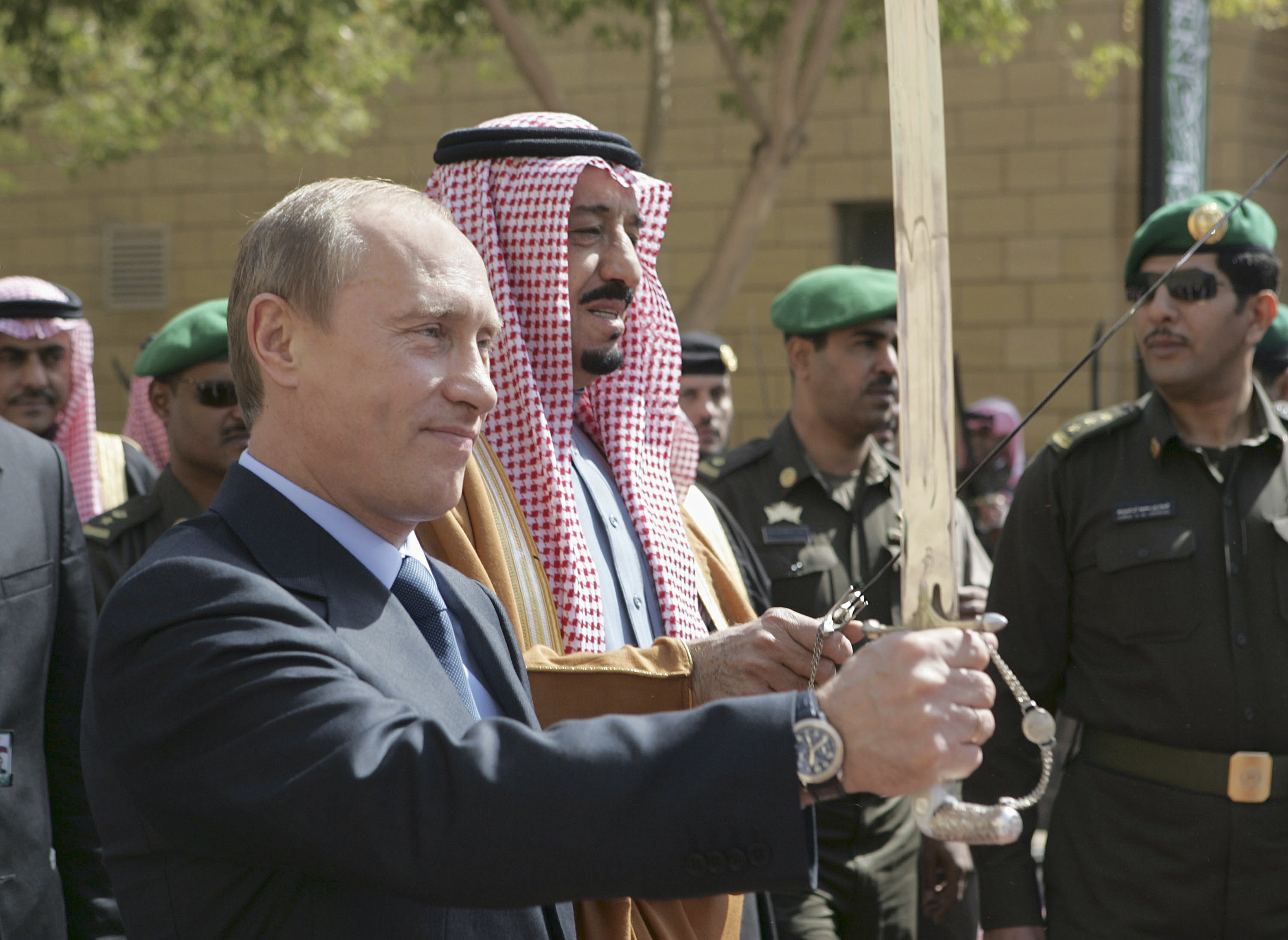 Russia's Vladimir Putin holds an ardah along side Saudi King Salman