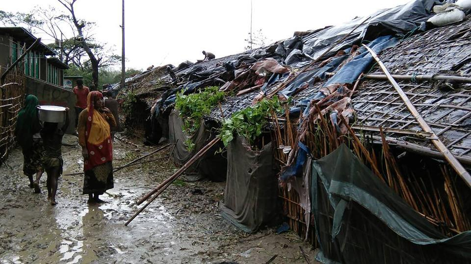Rohingya refugees walk next to huts in a makeshift camp in Bangladesh's Cox's Bazar district on May 30, 2017 after Cyclone Mora made landfall in the region.