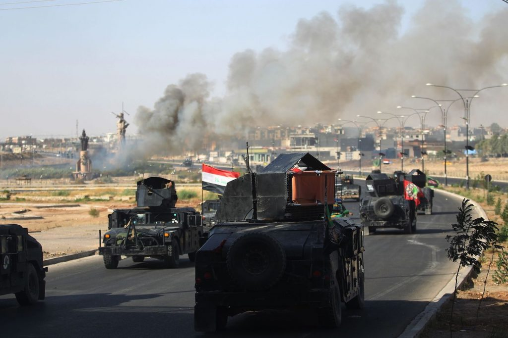 Smoke billows as Iraqi forces advance towards the centre of Kirkuk during an operation against Kurdish fighters on October 16, 2017. Iraqi forces seized the Kirkuk governor's office, key military sites and an oil field as they swept across the disputed province following soaring tensions over an independence referendum.