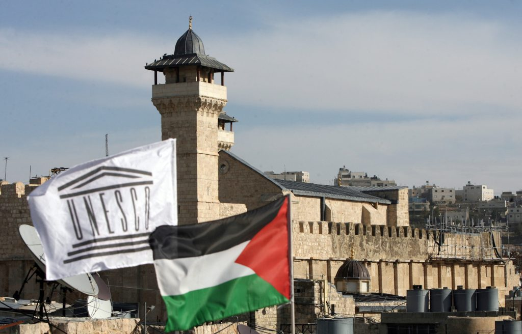 The Palestinian Rehabilitation Committee raised the UNESCO flag next to the national Palestinian flag in front of Hebron's Ibrahimi Mosque or the Tomb of the Patriarchs in the southern West Bank city's old quarter on December 13, 2011, as the Palestinian flag was hoisted at the UNESCO headquarters in Paris, a month after the Palestinians' admission to the UN cultural agency sparked anger and reprisals from the United States and Israel.