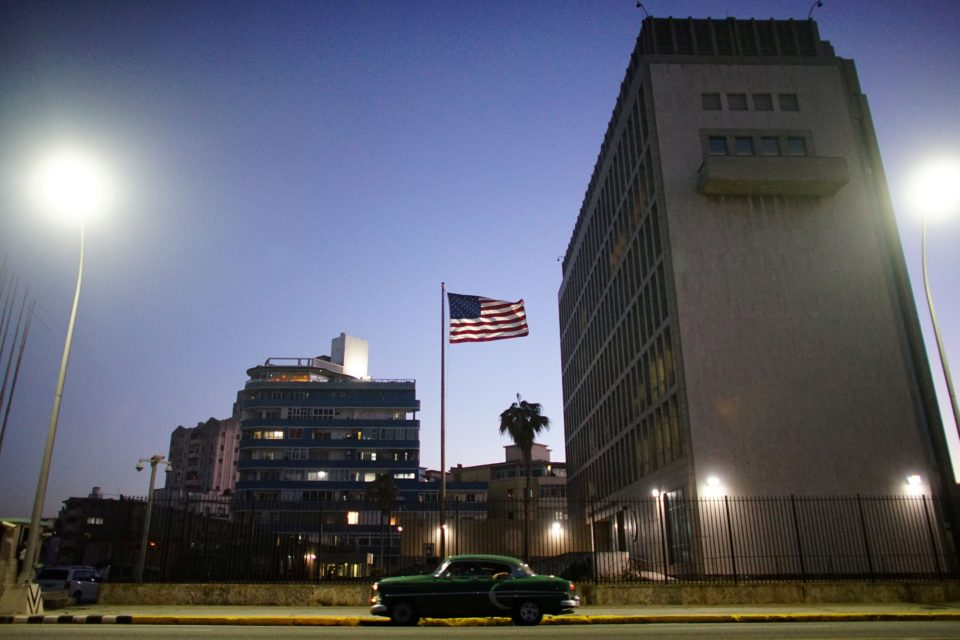 A vintage car passes by in front of the US Embassy in Havana, Cuba