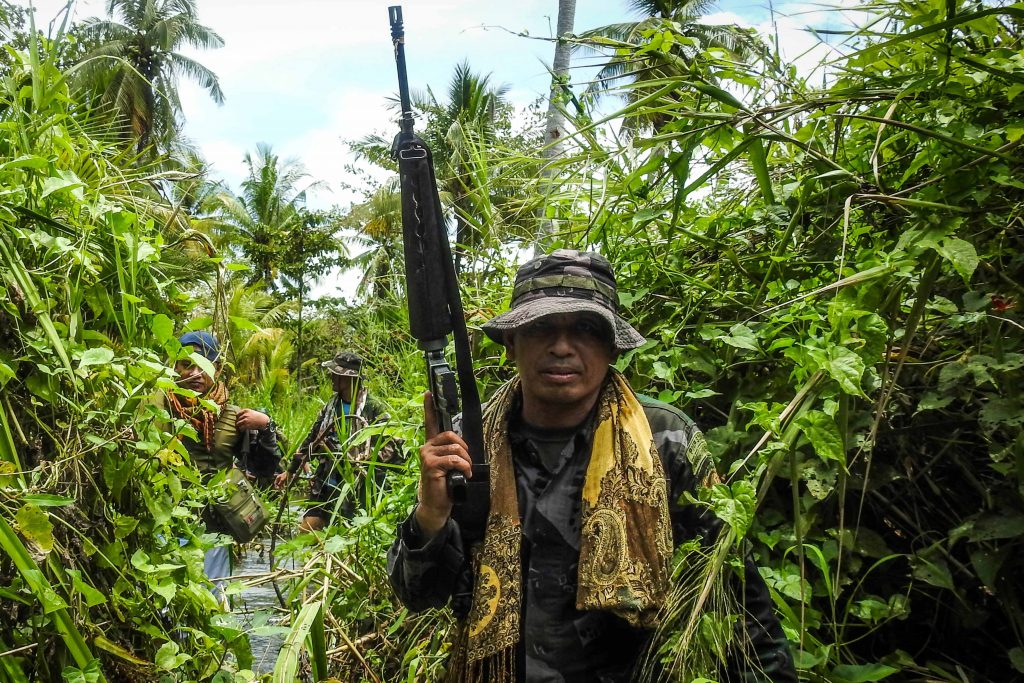 """A government police officer along with members of the Moro Islamic Liberation Front (MILF-back) wading through a flooded farm on their way to the frontline in Datu Salibo town, Maguindanao province, in southern island of Mindanao. The Philippines' largest Muslim rebel group said on August 23 it had lost 10 fighters in battles to stop a """"growing force"""" of radical militants who support the Islamic State group."""