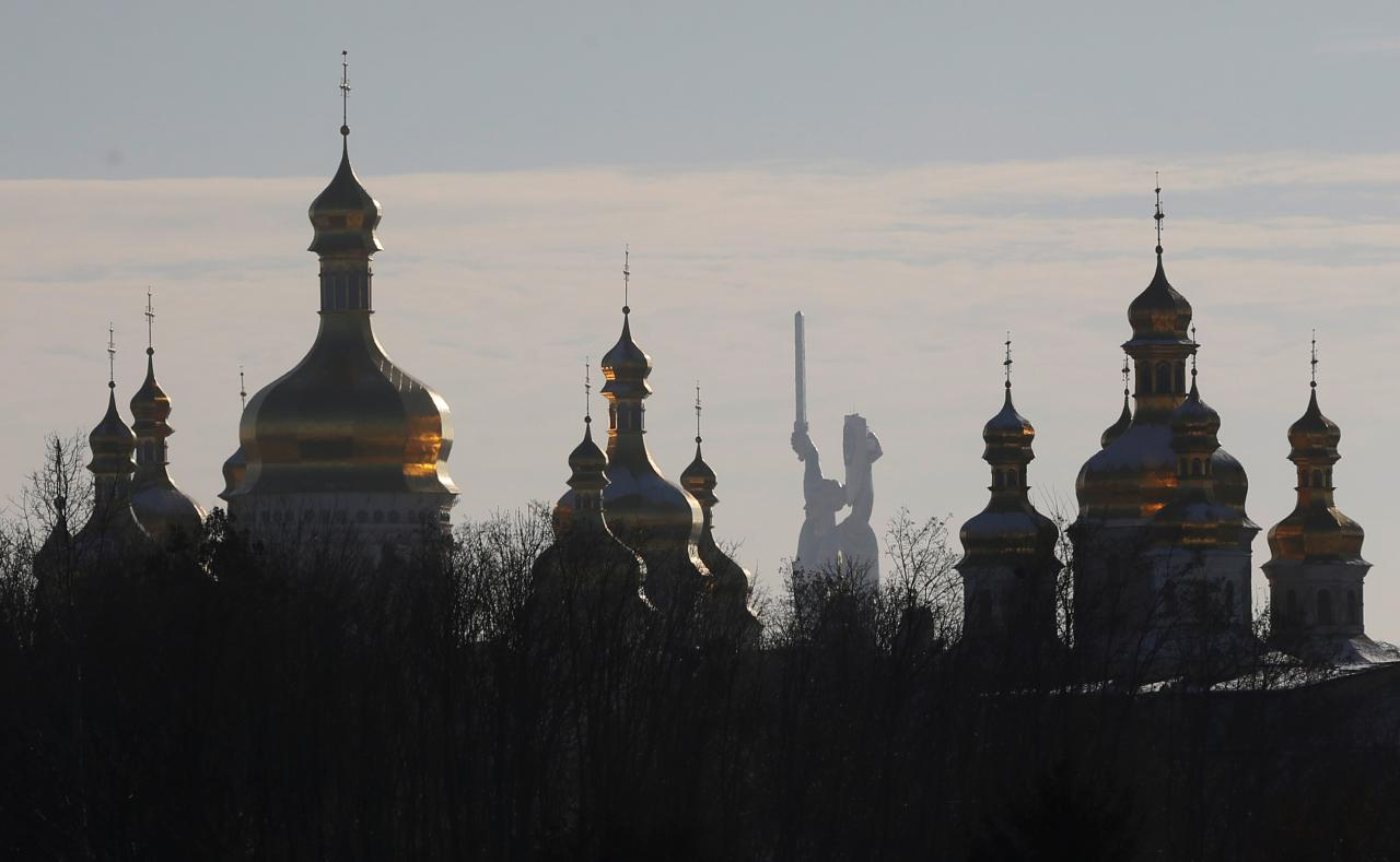 Domes of the Dormition Cathedral of the Kiev Pechersk Lavra monastery are seen in front of the Mother Homeland monument in Kiev